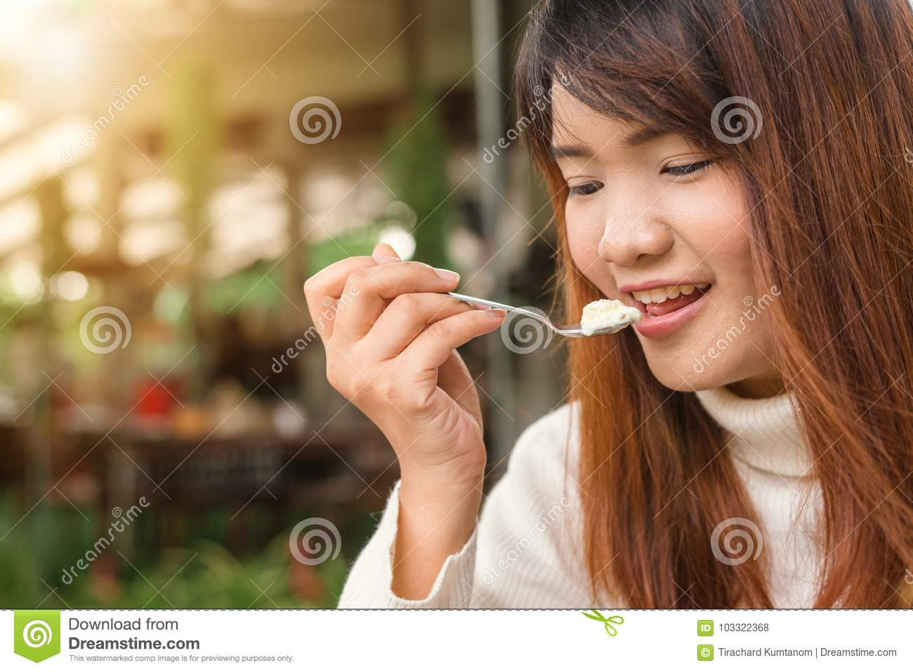 Attractive happy cute young asian woman sitting and eating dessert at outdoors cafe. Food, junk-food, culinary, baking and holiday
