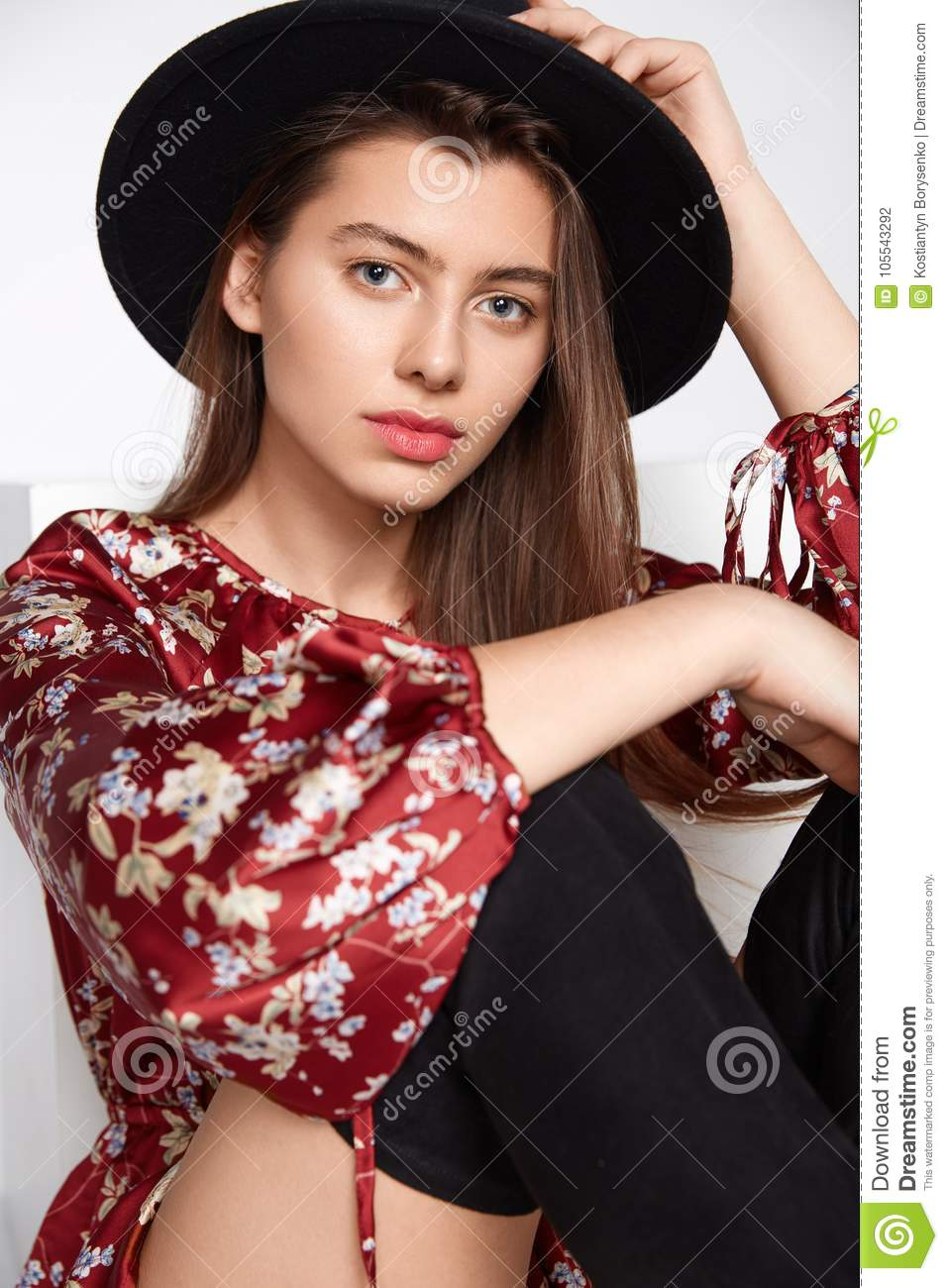 Attractive happy girl is possing and smilling in flower red dress and black  hat on white 134d63a746c