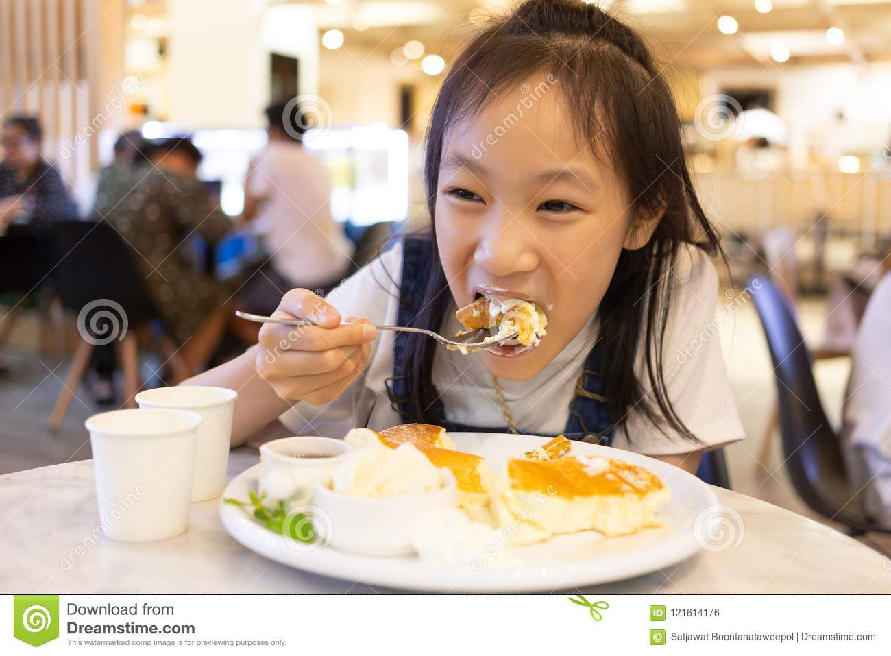 Attractive happy girl sitting and eating dessert,Close up portrait of a hungry greedy girl eating panckaces in the restaurant