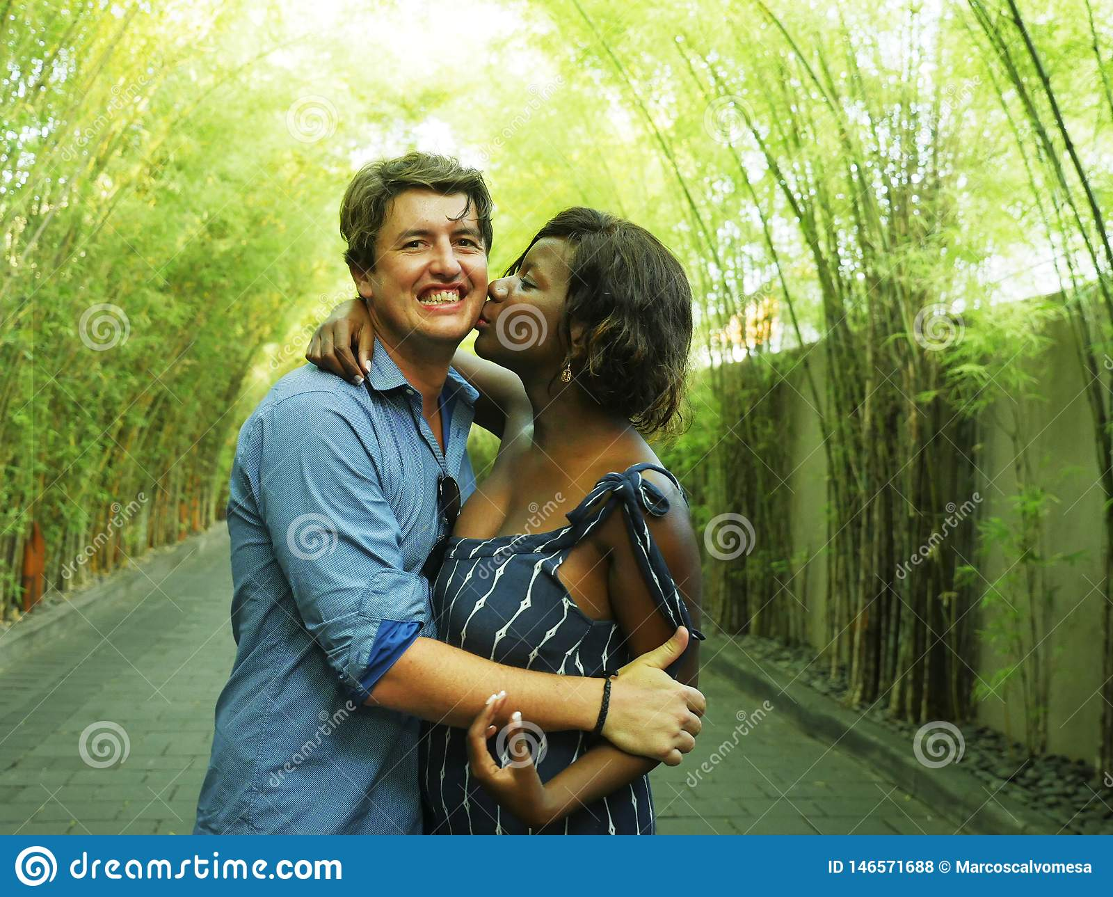 Attractive and happy mixed ethnicity couple cuddling outdoors with attractive black afro American girlfriend or wife and handsome