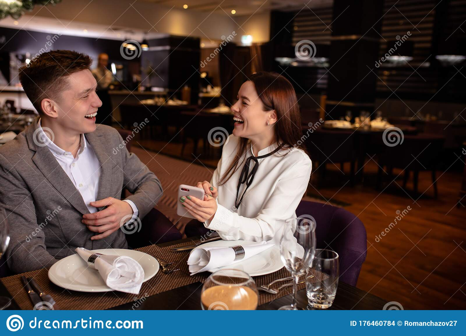 Positive Woman Happily Tell Interesting Story To Boyfriend In Restaurant Use Mobile Phone Stock Photo Image Of Love Gentleman 176460784