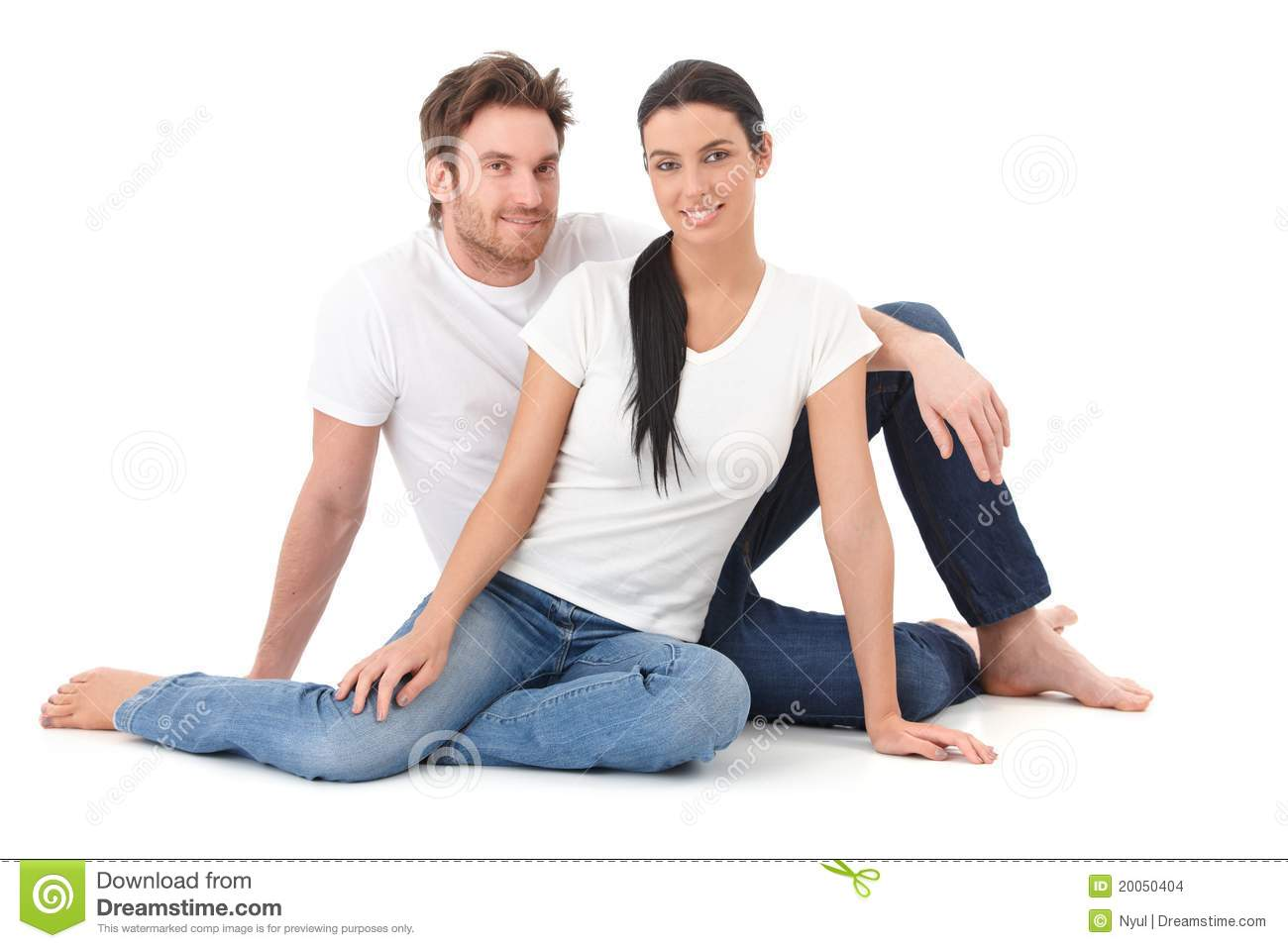 Attractive loving couple sitting on floor smiling