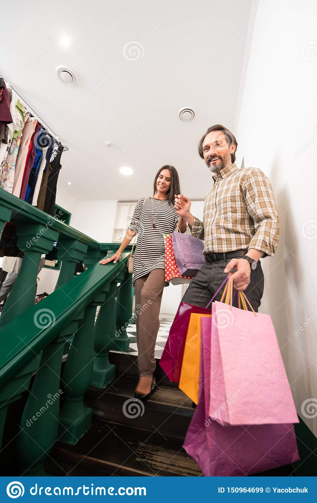 Attractive man assisting nice-looking lady with shopping bags