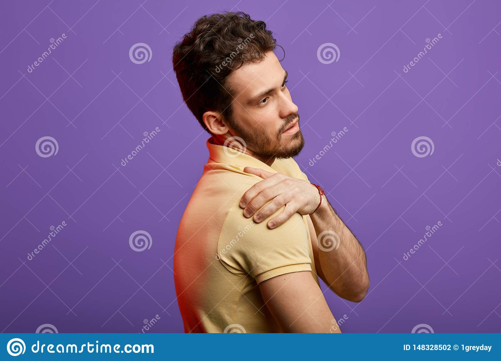Attractive man suffering from pain in his shoulder