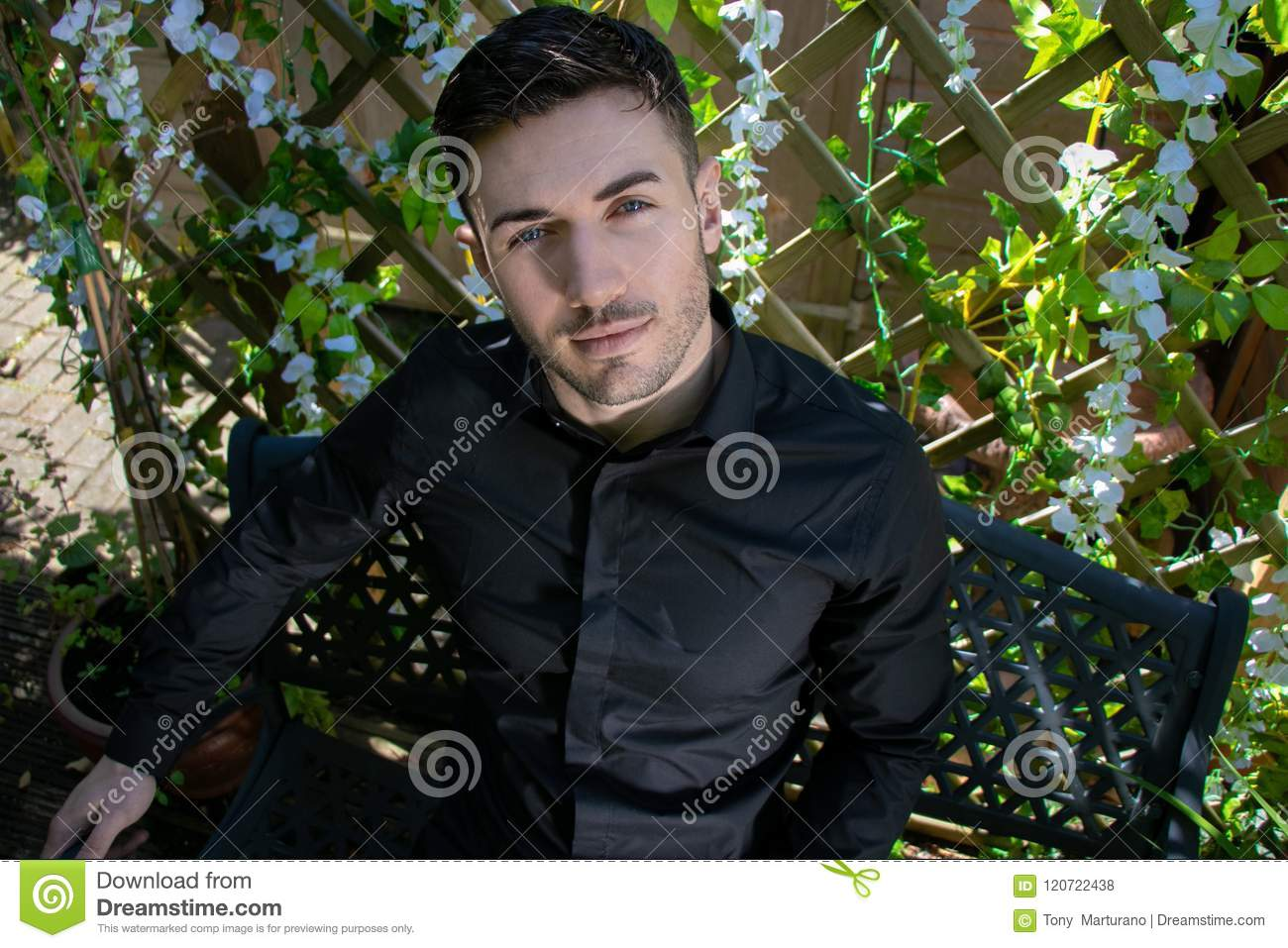 Handsome Man Wearing Black Shirt With Blue Eyes And Beard Looks Into