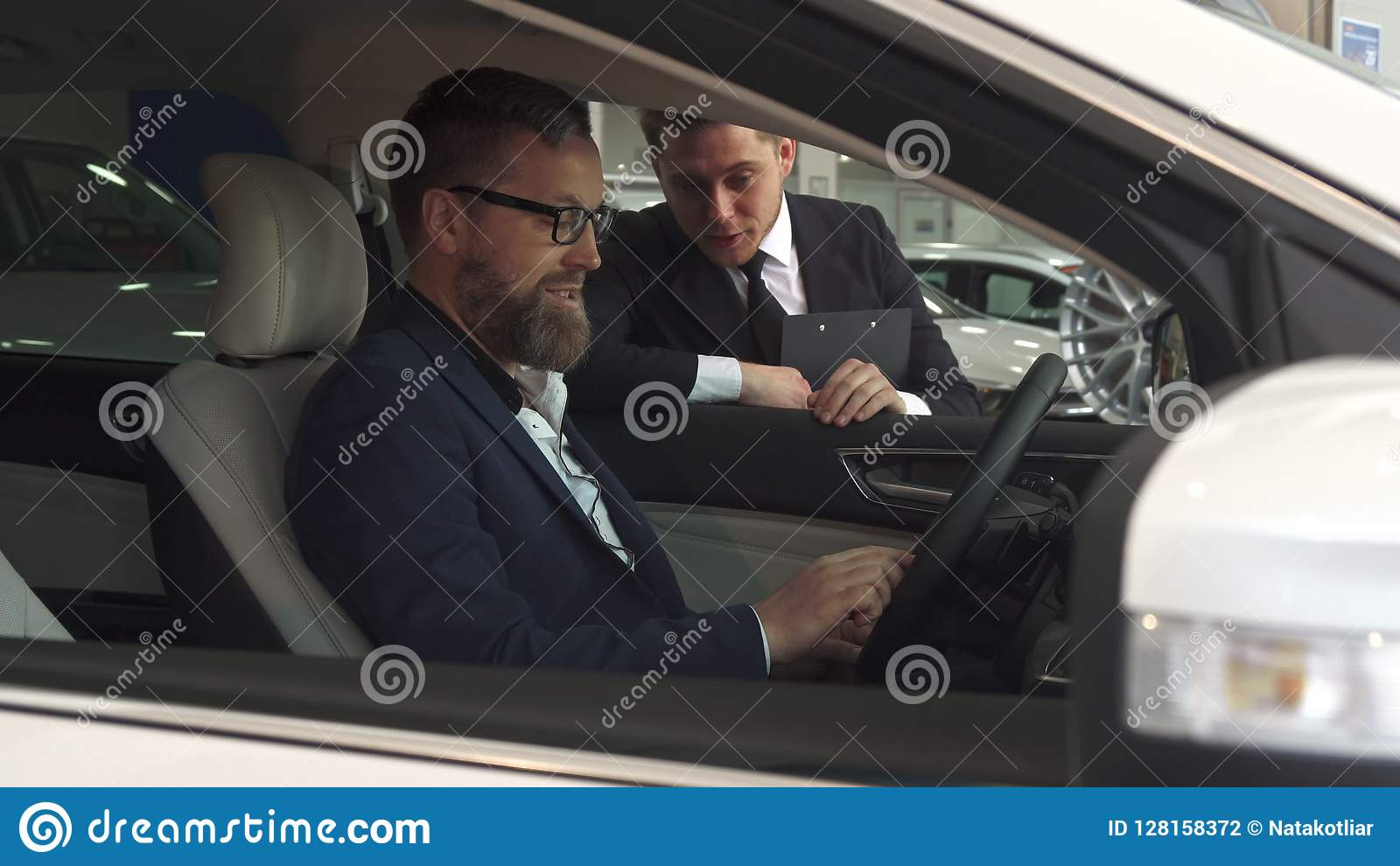 Sales manager comes to the car with customer inside it