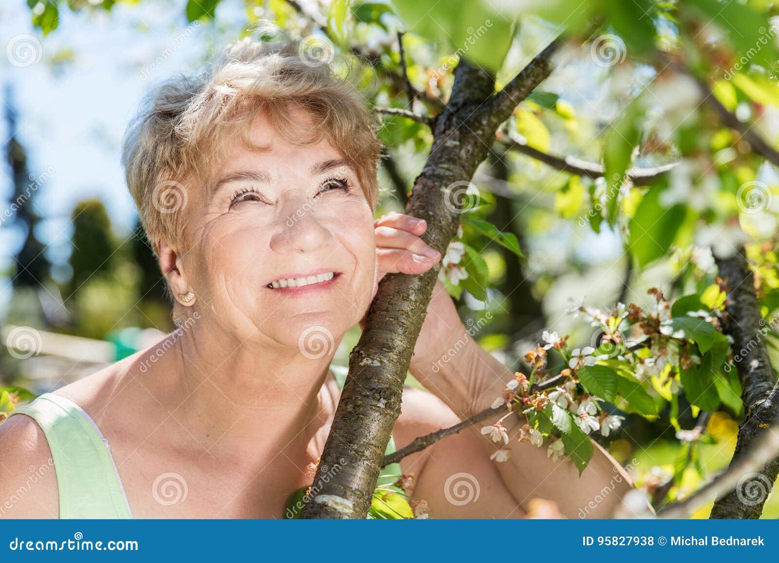 Attractive mature woman embracing nature. Grandmother