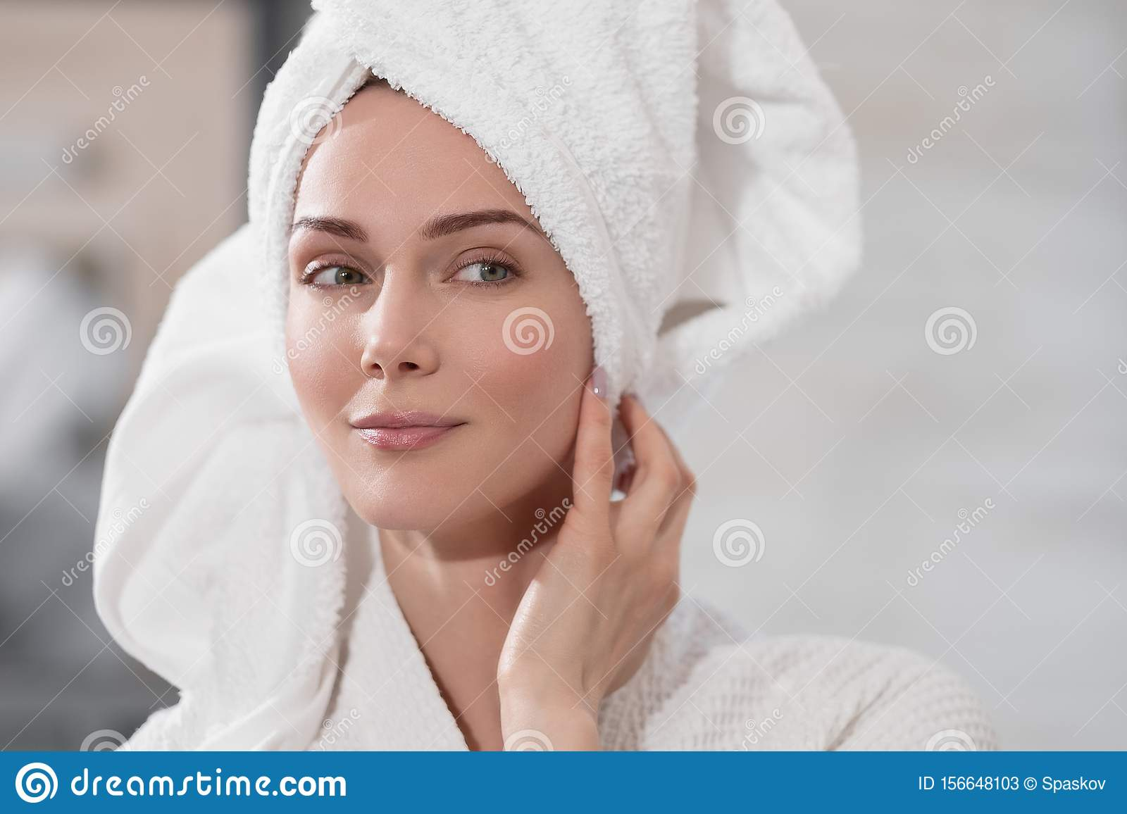 Attractive middle-aged blond woman with white towel on her head and in bathrobe standing in the bathroom by the mirror