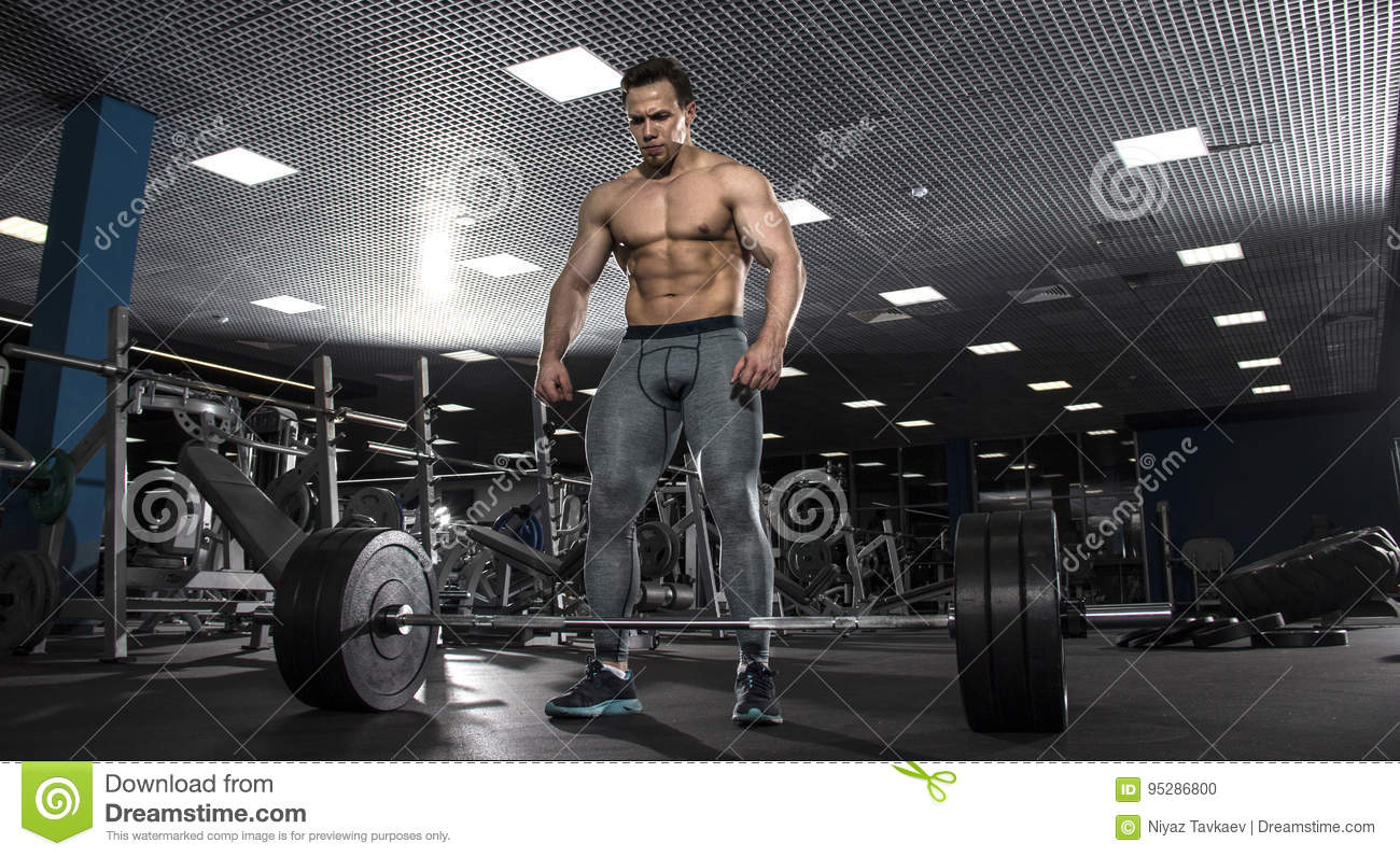 Attractive muscular shirtless athlete preparing to do deadlift i