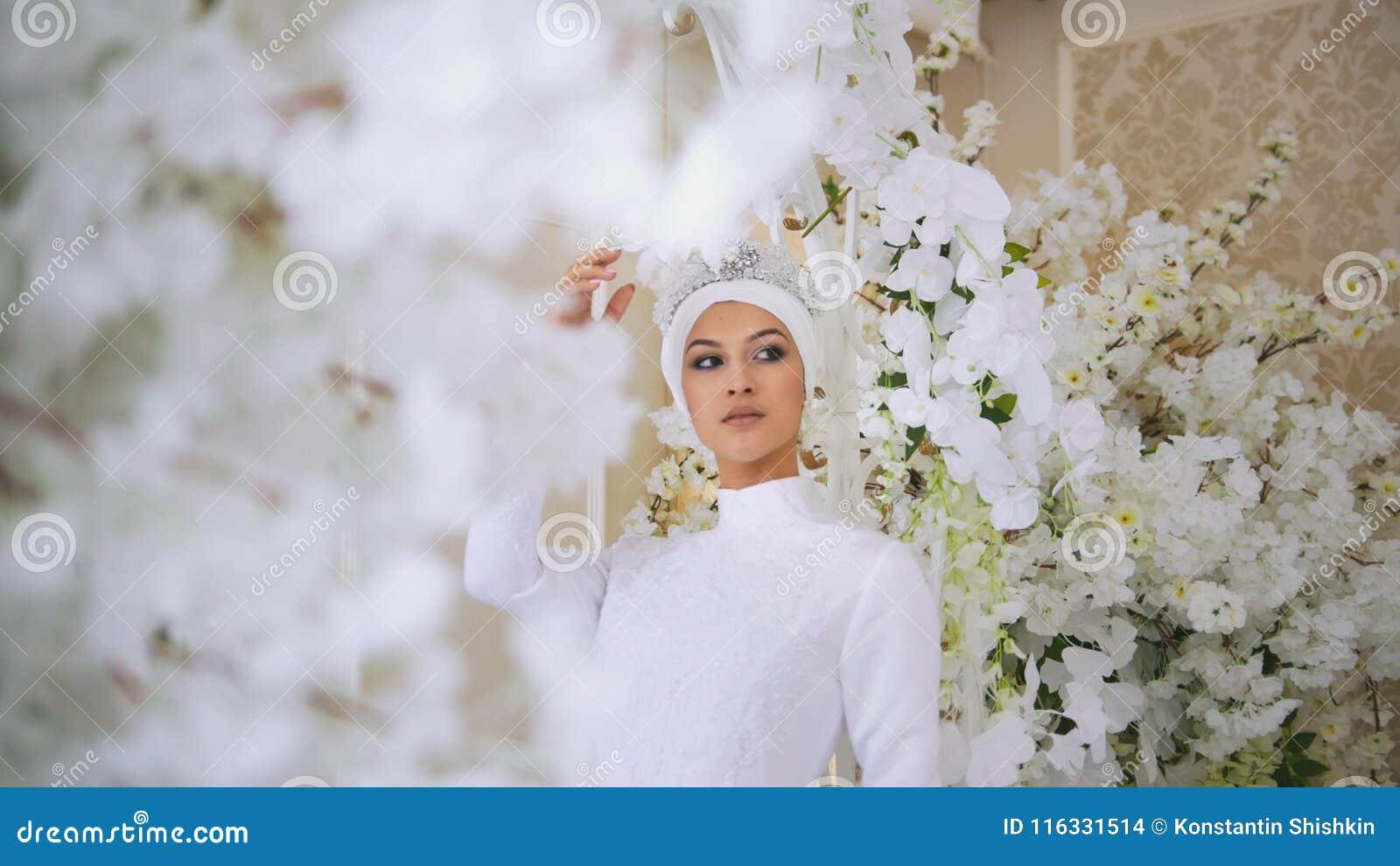 Attractive Muslim Bride With Tiara In Weddind Dress In White Flowers