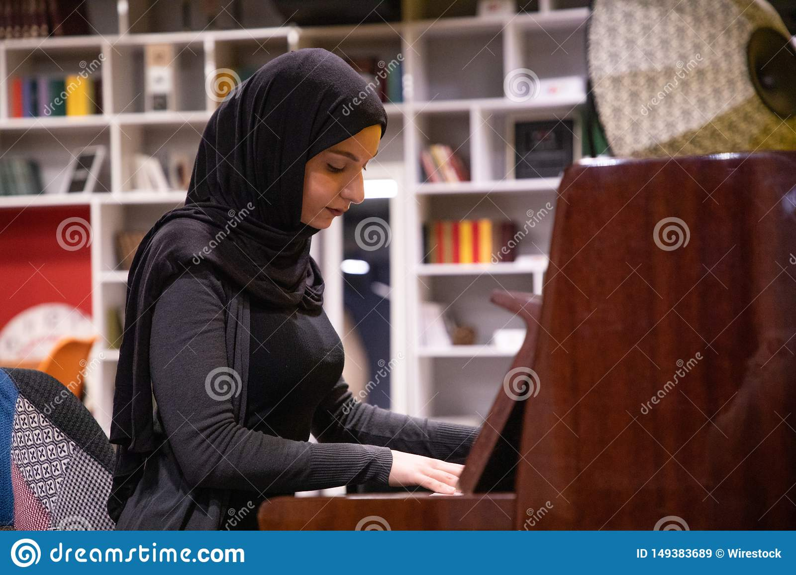 Attractive Muslim female in a hijab playing piano