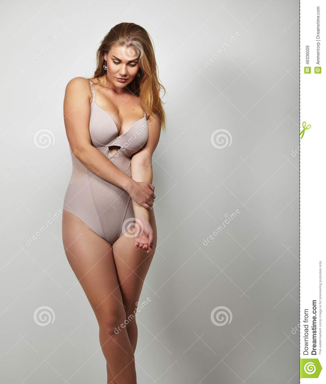 Portrait of a voluptuous woman in lingerie looking down on grey background.  Attractive plus size young lady in body stocking. 24e256277
