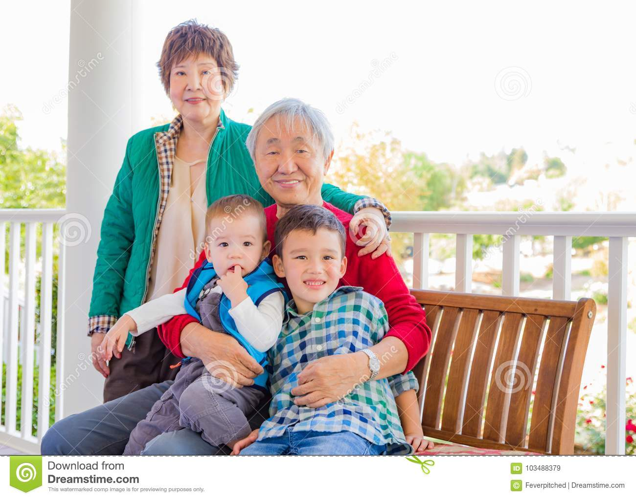 Attractive Senior Adult Chinese Couple Sitting With Their Mixed Race Grandc
