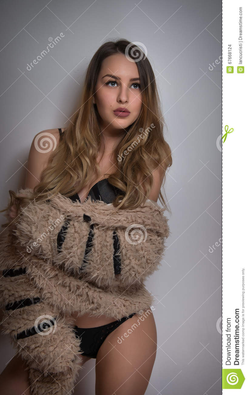 827b452f2 Attractive blonde in black lingerie posing provocatively indoor. Portrait of  sensual woman wearing brown fluffy