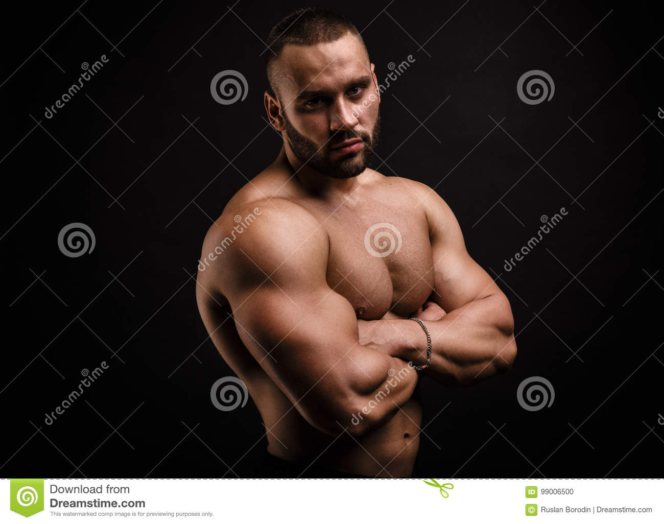 Serious And Shirtless Bodybuilder Crossing Hands On A Muscular Chest