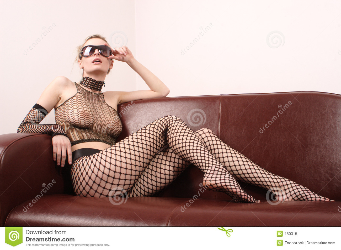 Attractive woman in sunglasses sitting on sofa