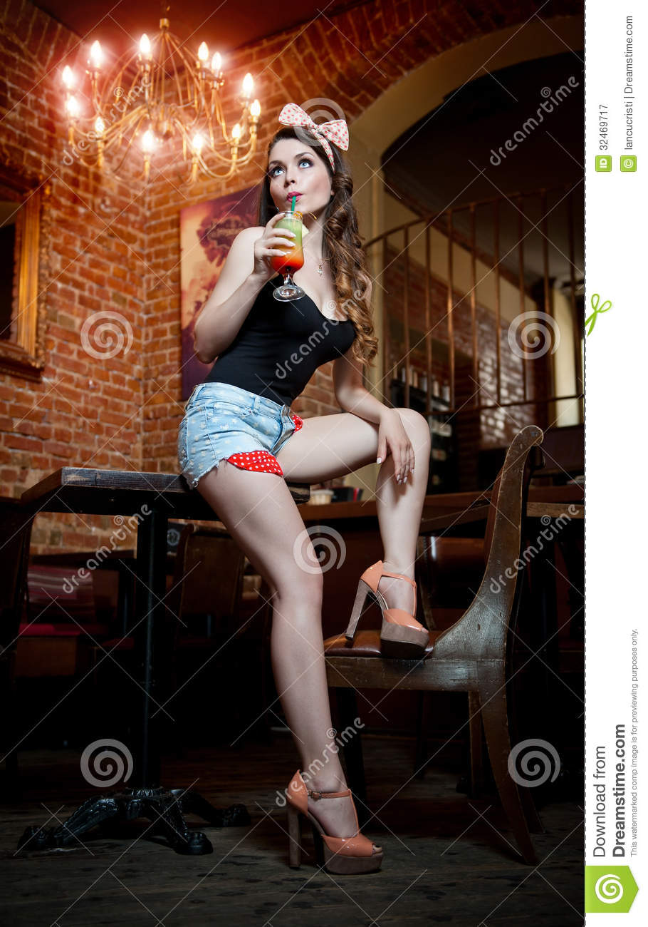 Attractive Smiling Pinup Woman In Denim Shorts Sitting On
