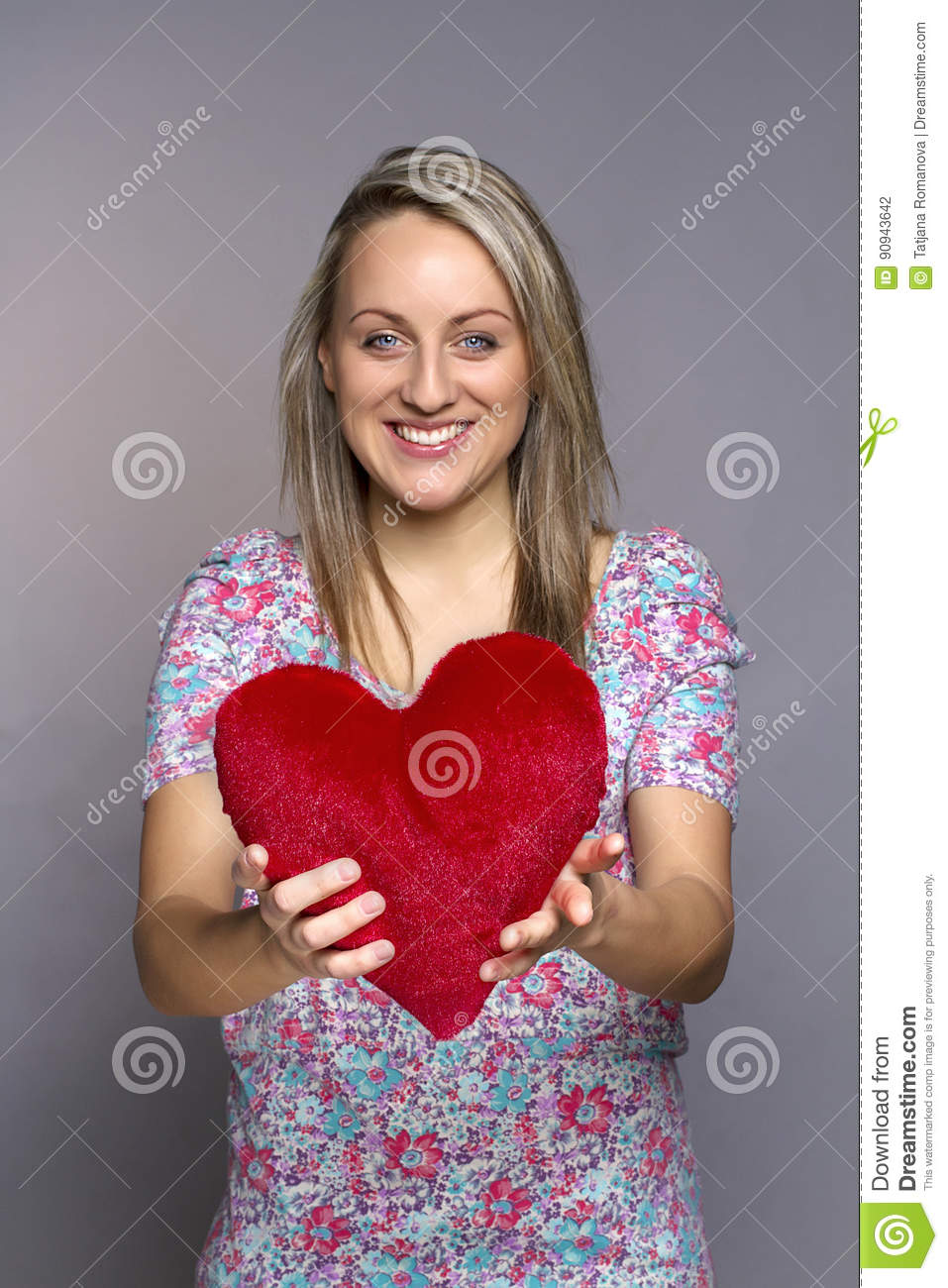 Attractive smiling woman holding a red heart