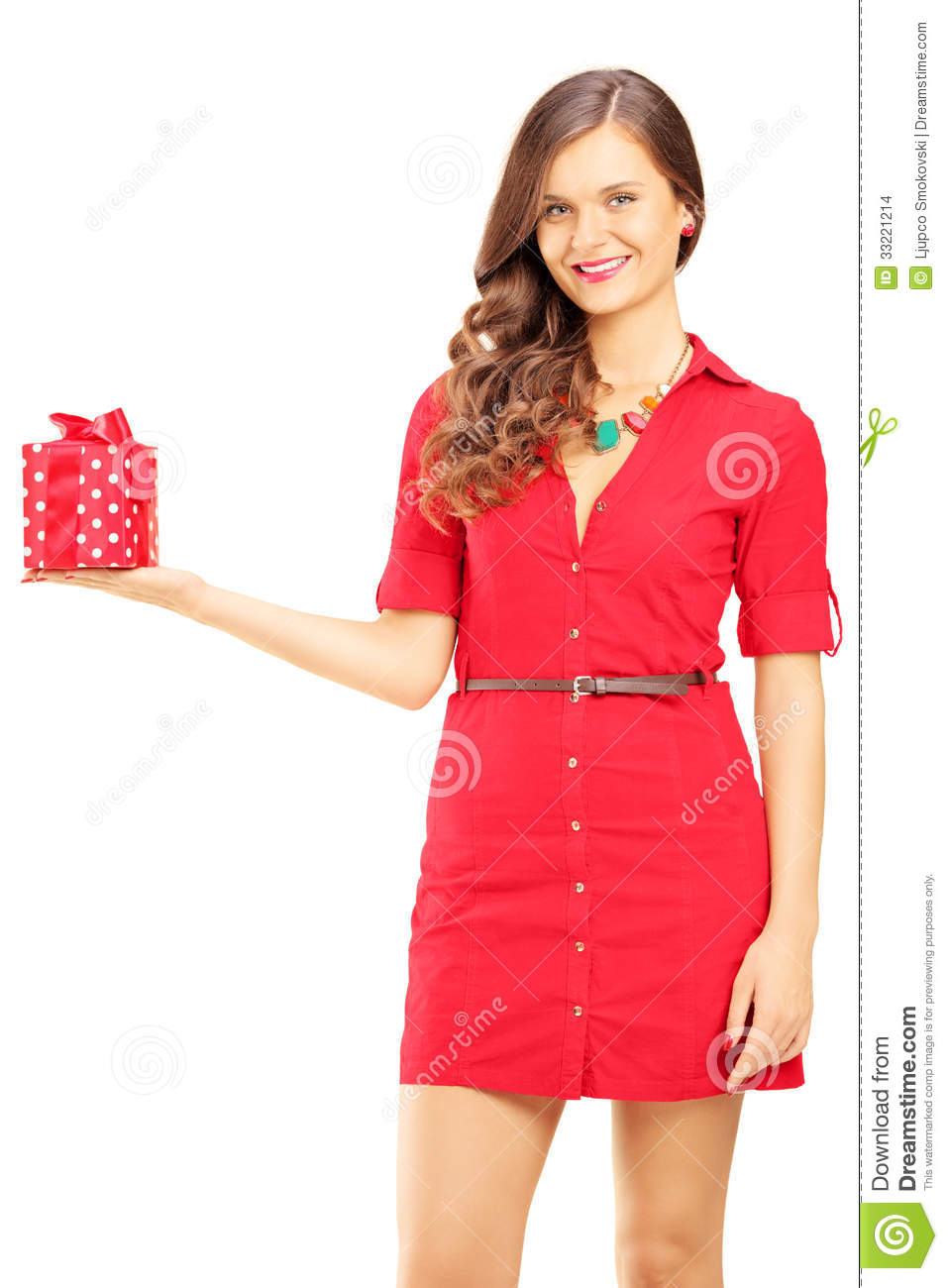 Attractive smiling woman in red dress holding a gift box stock images