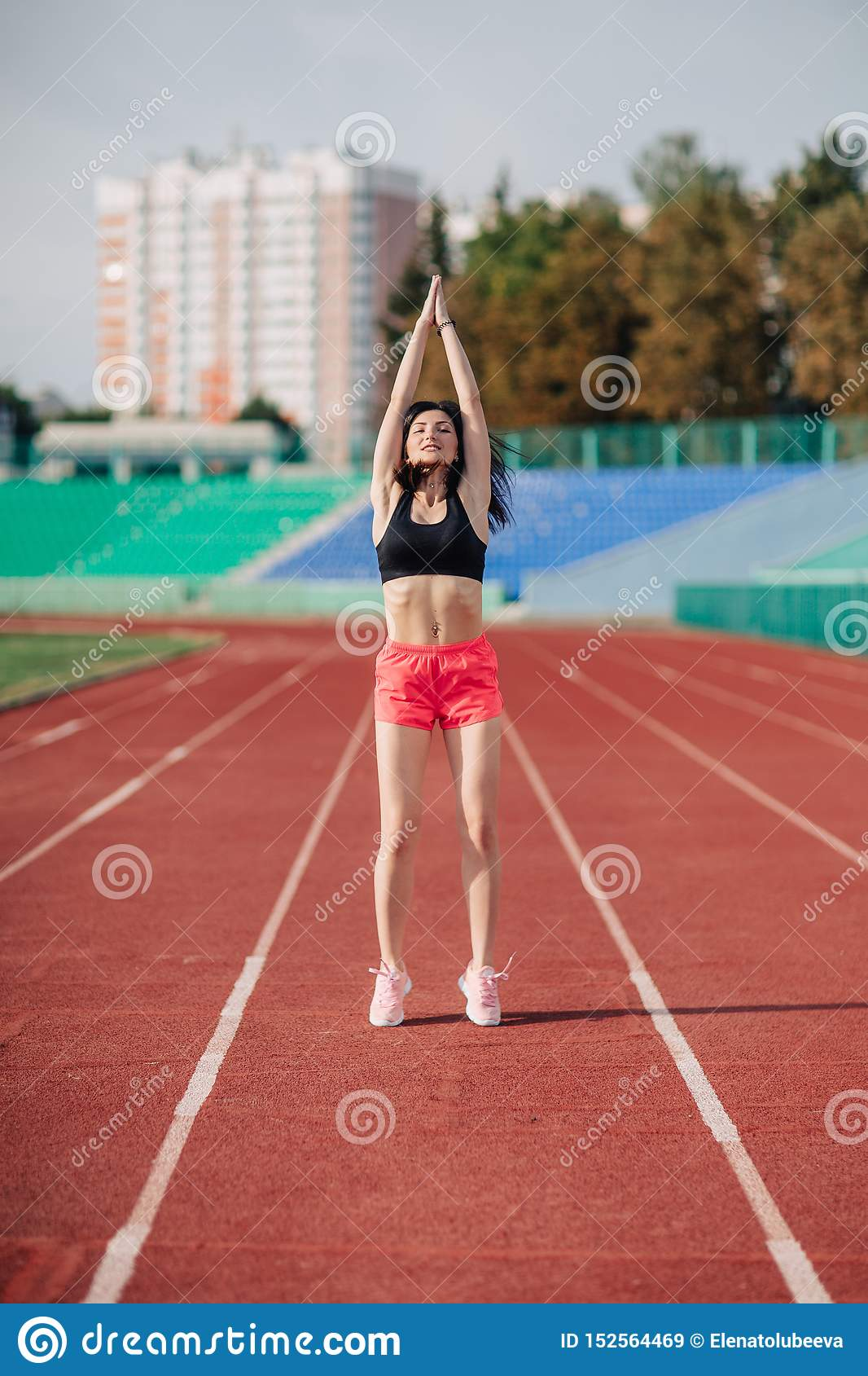 Attractive sporty brunette woman in pink shorts and top doing workout with jump rope in sun rays at the stadium