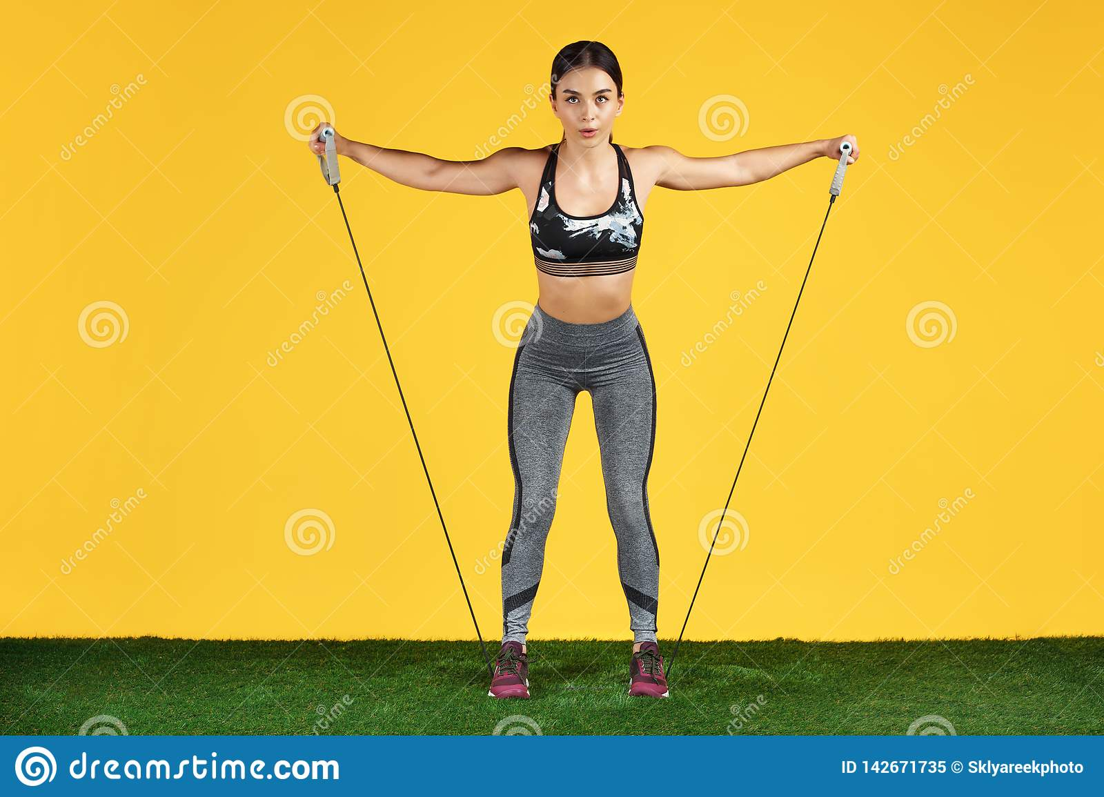 Attractive sporty young woman workout with stretch bands on the green grass over yellow background.