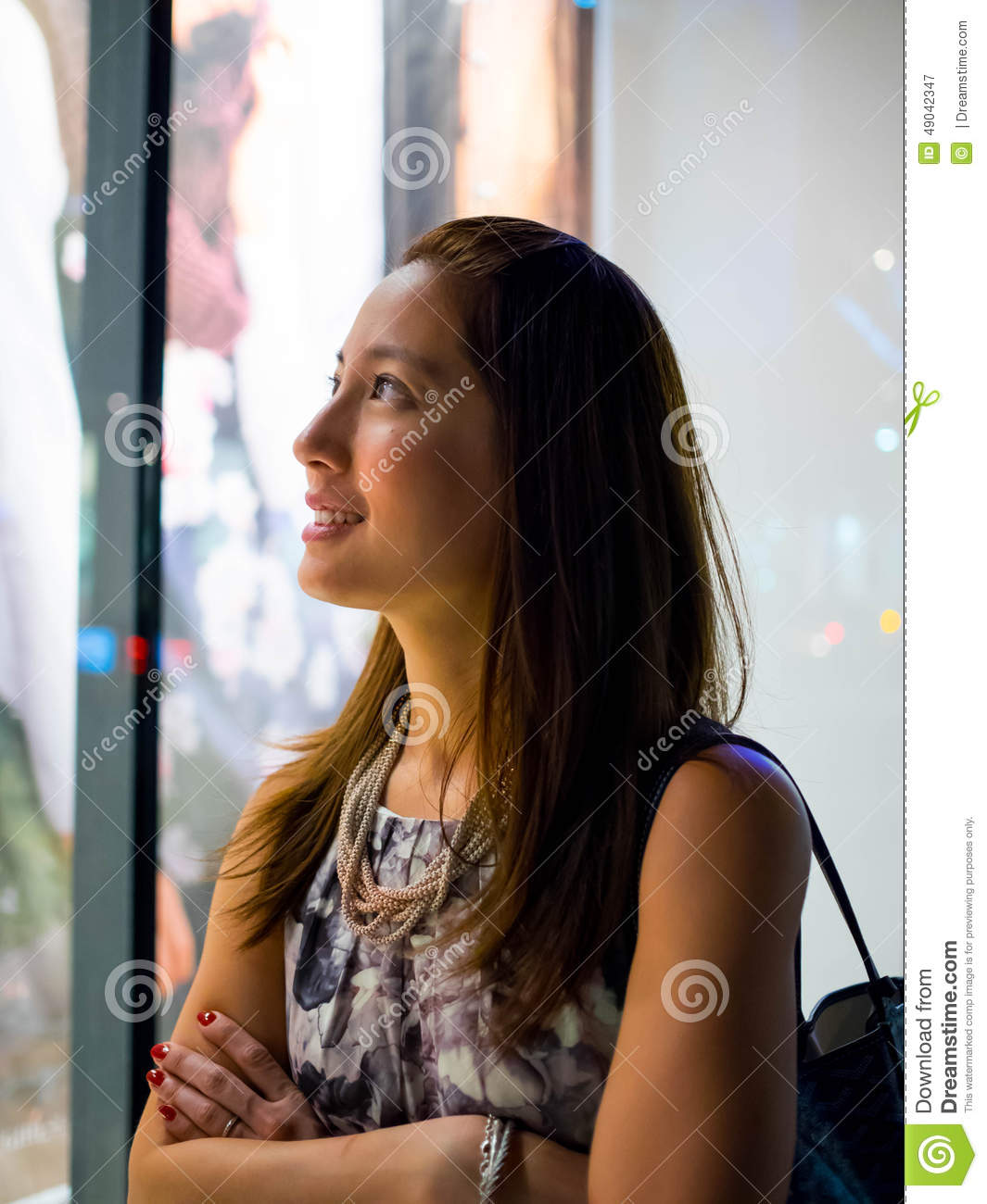 Attractive, stylish, fashionable young asian woman window shopping