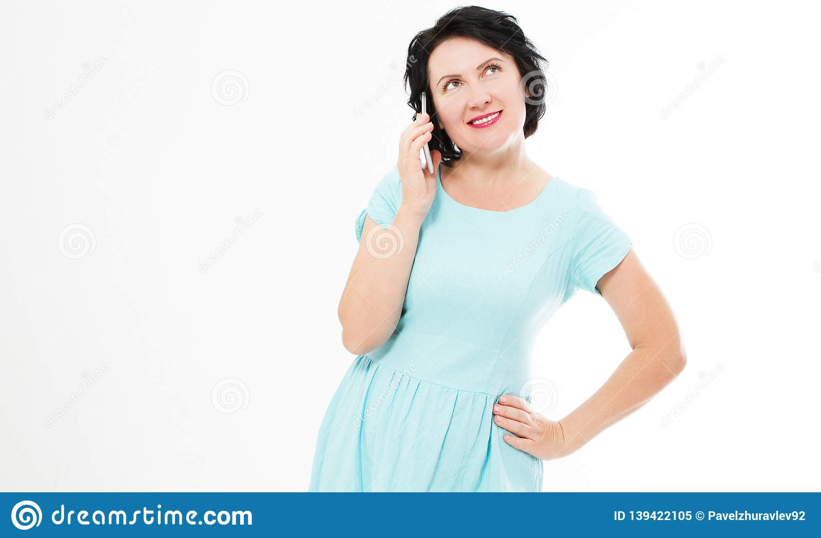 Attractive, successful and happy middle aged brunette woman in blue dress female using mobile cell phone