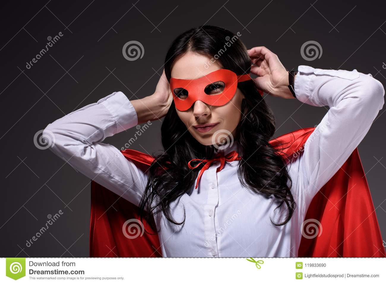 attractive super businesswoman in red cape tying mask