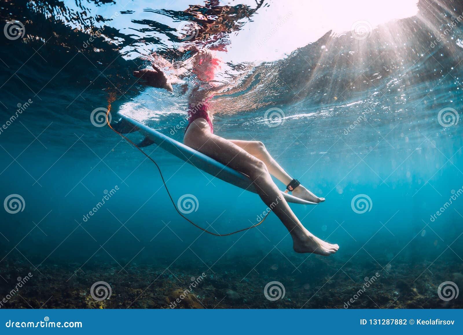 Attractive surfer girl sit at surfboard underwater in ocean