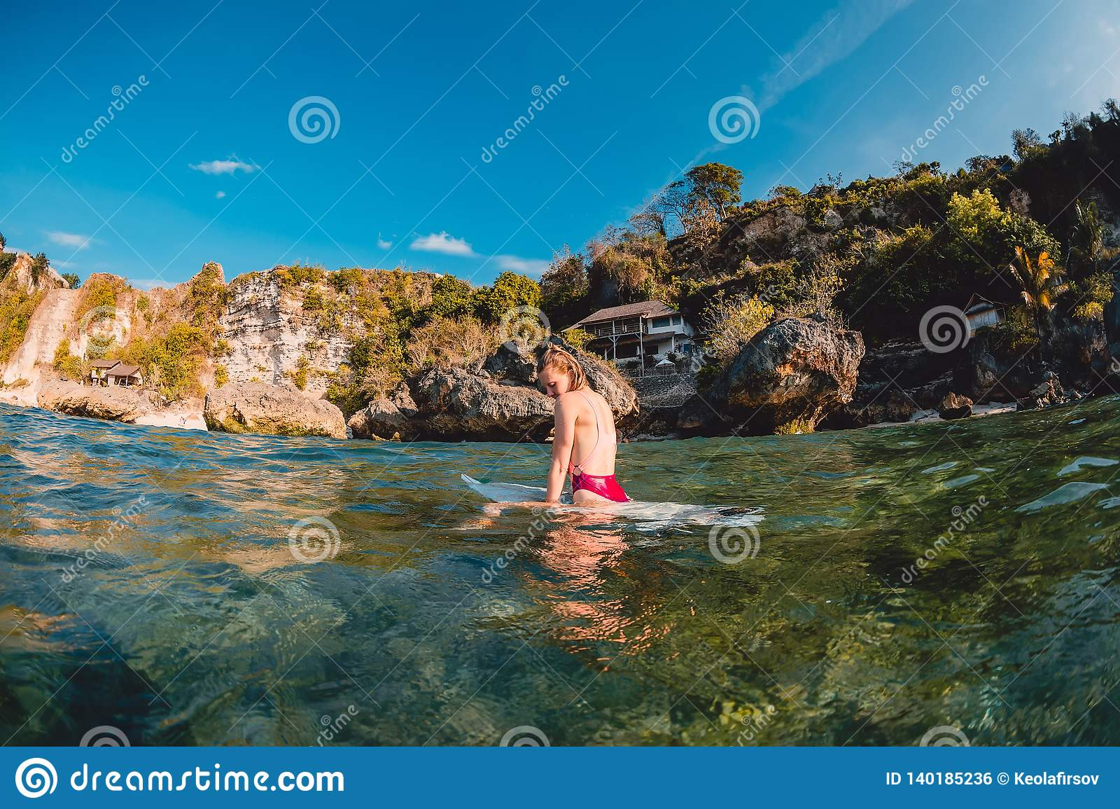 Attractive surfer girl with surfboard. Surfer sit at board