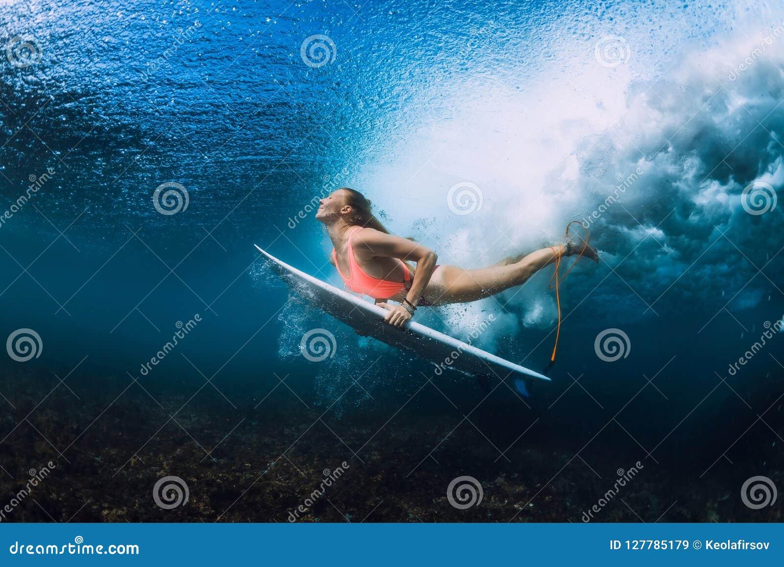 Attractive surfer woman dive underwater with under wave.