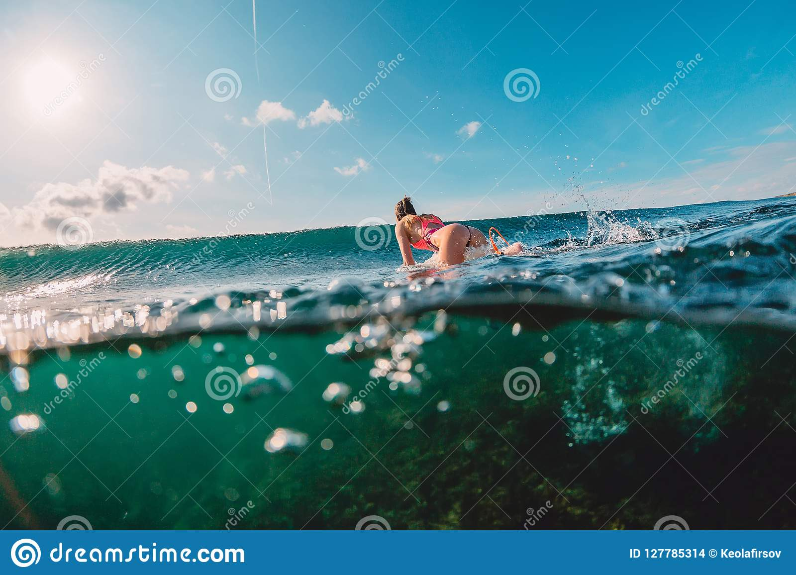 Attractive surfer woman in ocean and wave. Surf girl make duck dive.