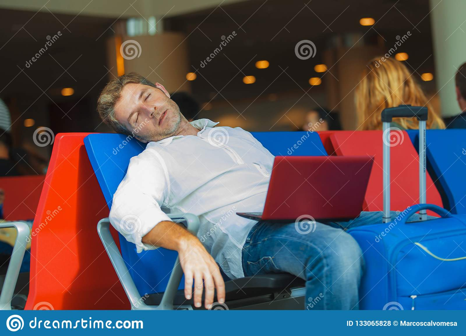 Attractive and tired traveler man with luggage taking a nap sleeping while working with laptop computer waiting for flight at