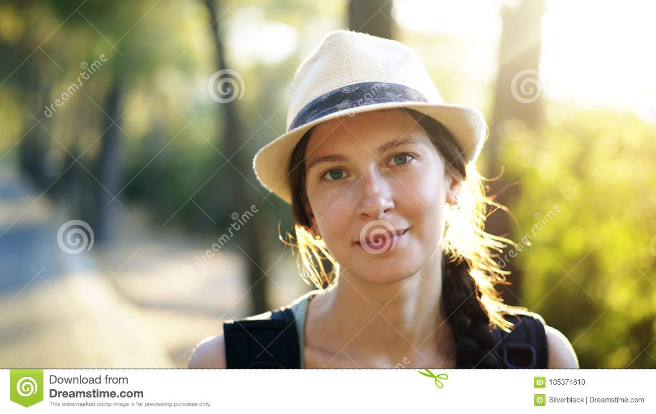 Closeup portrait of attractive tourist girl smiling and looking into camera while hiking beautiful forest