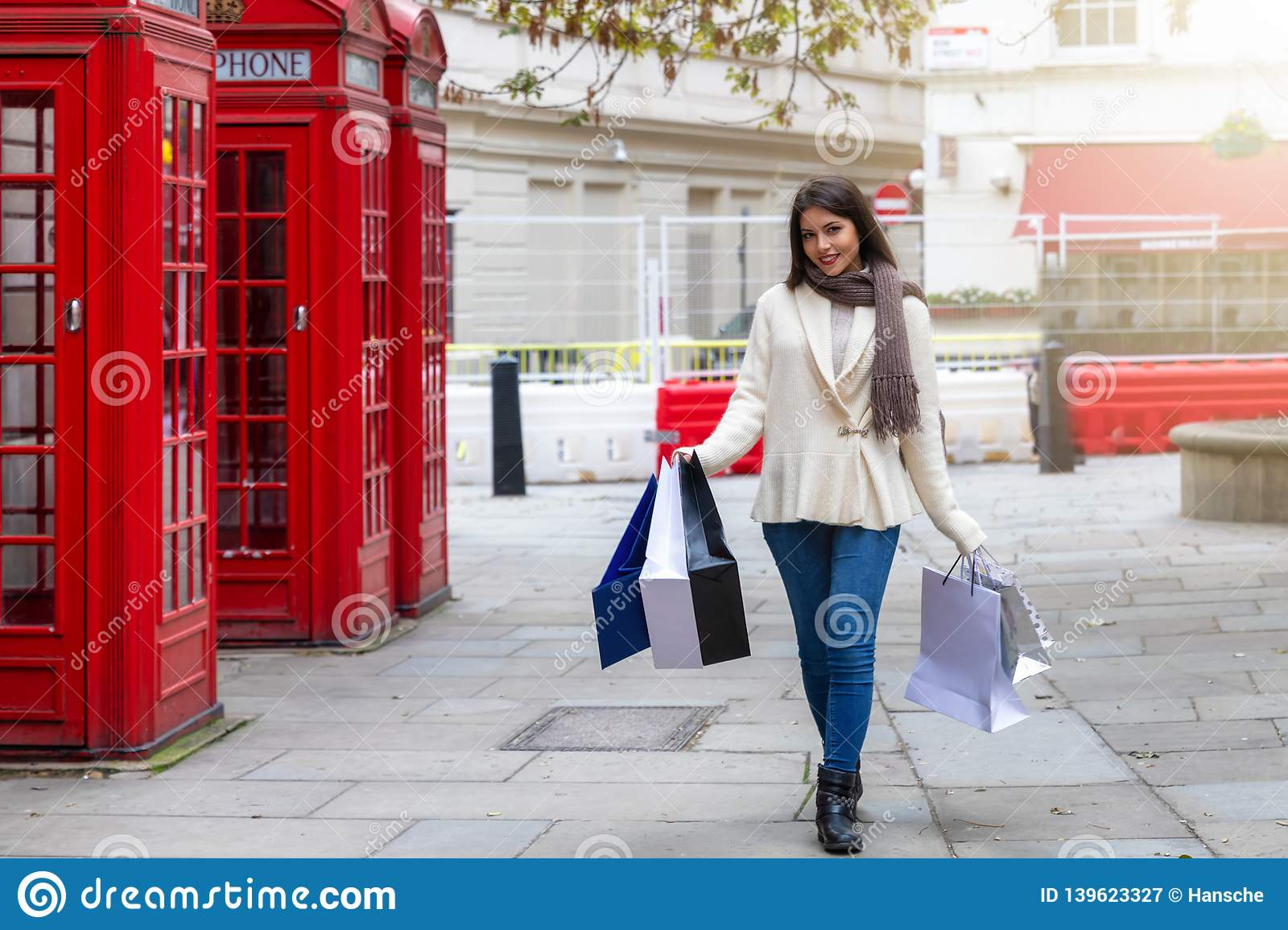 City shopping woman walks along red telephone booths in London, UK