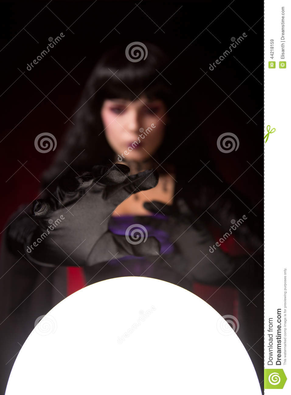 Attractive witch or fortune teller reaches for a crystal ball