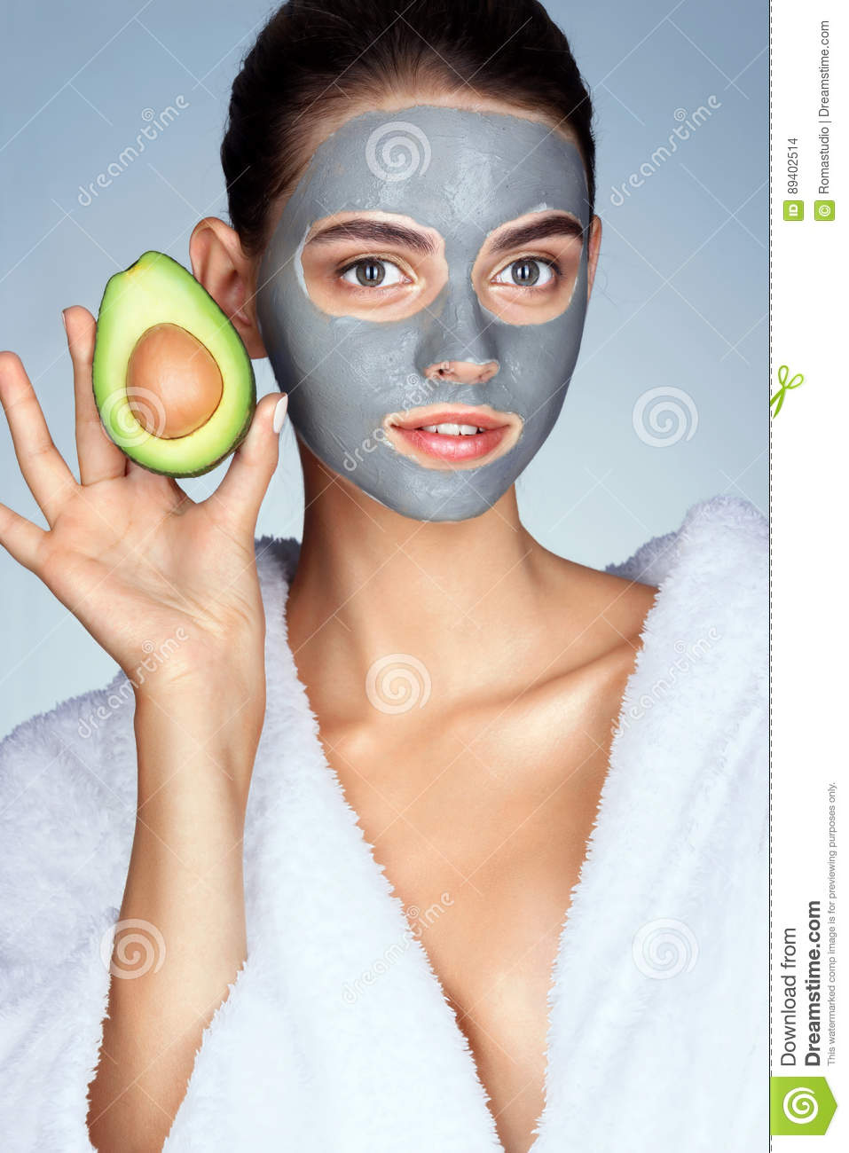 Attractive woman holding half an avocado in hand.
