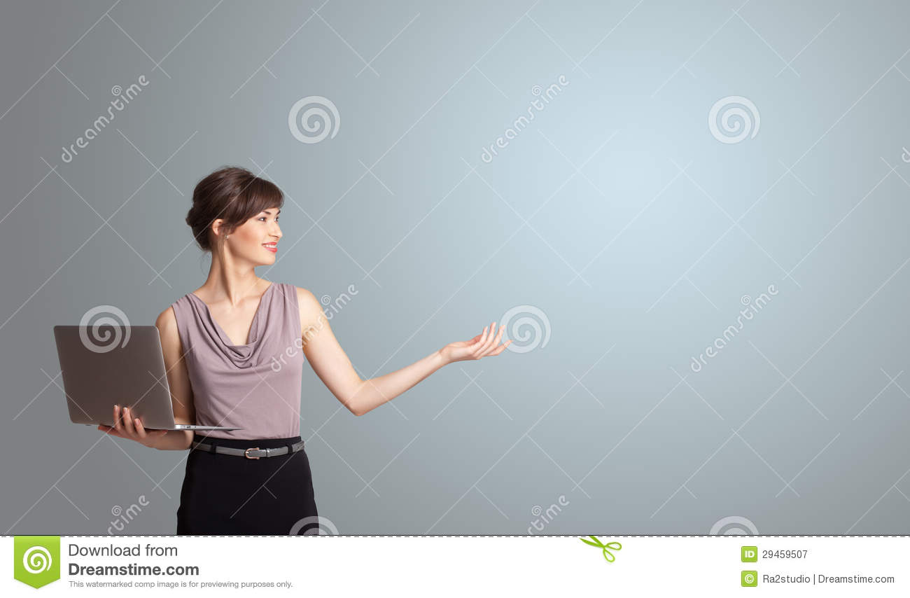 Attractive woman holding a laptop with copy space