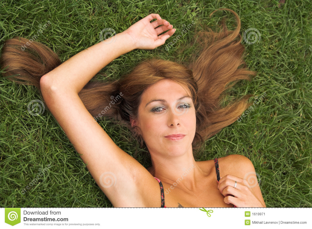 Mature Woman Lying On Grass Resting On Elbows Smiling