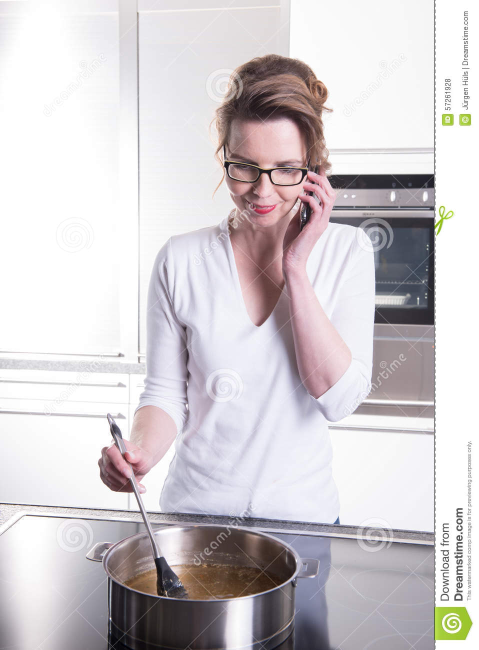 Attractive woman in modern ktchen cooking and on the phone