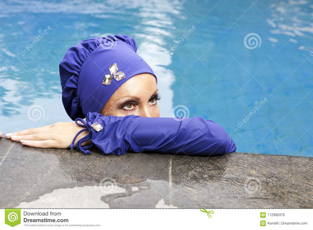 Attractive woman in a Muslim swimwear burkini in the pool, a close up on eyes