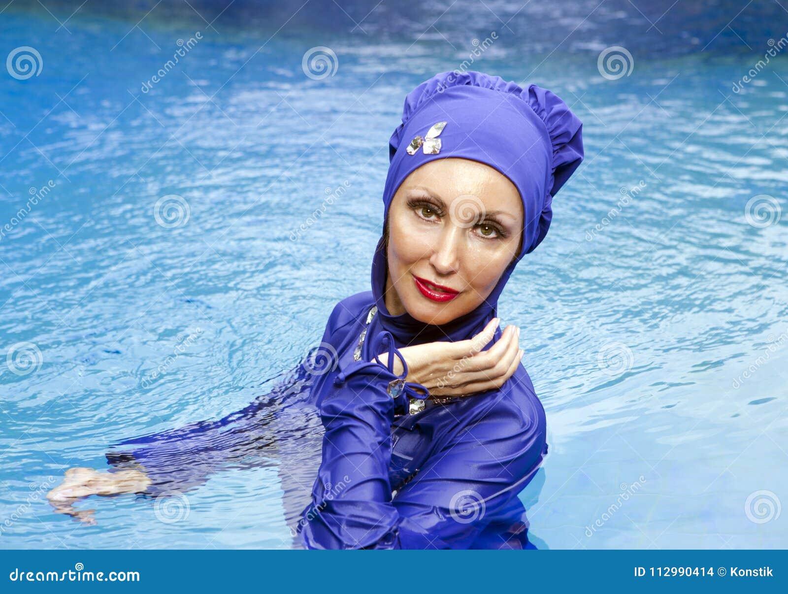 Attractive woman in a Muslim swimwear burkini in the sea