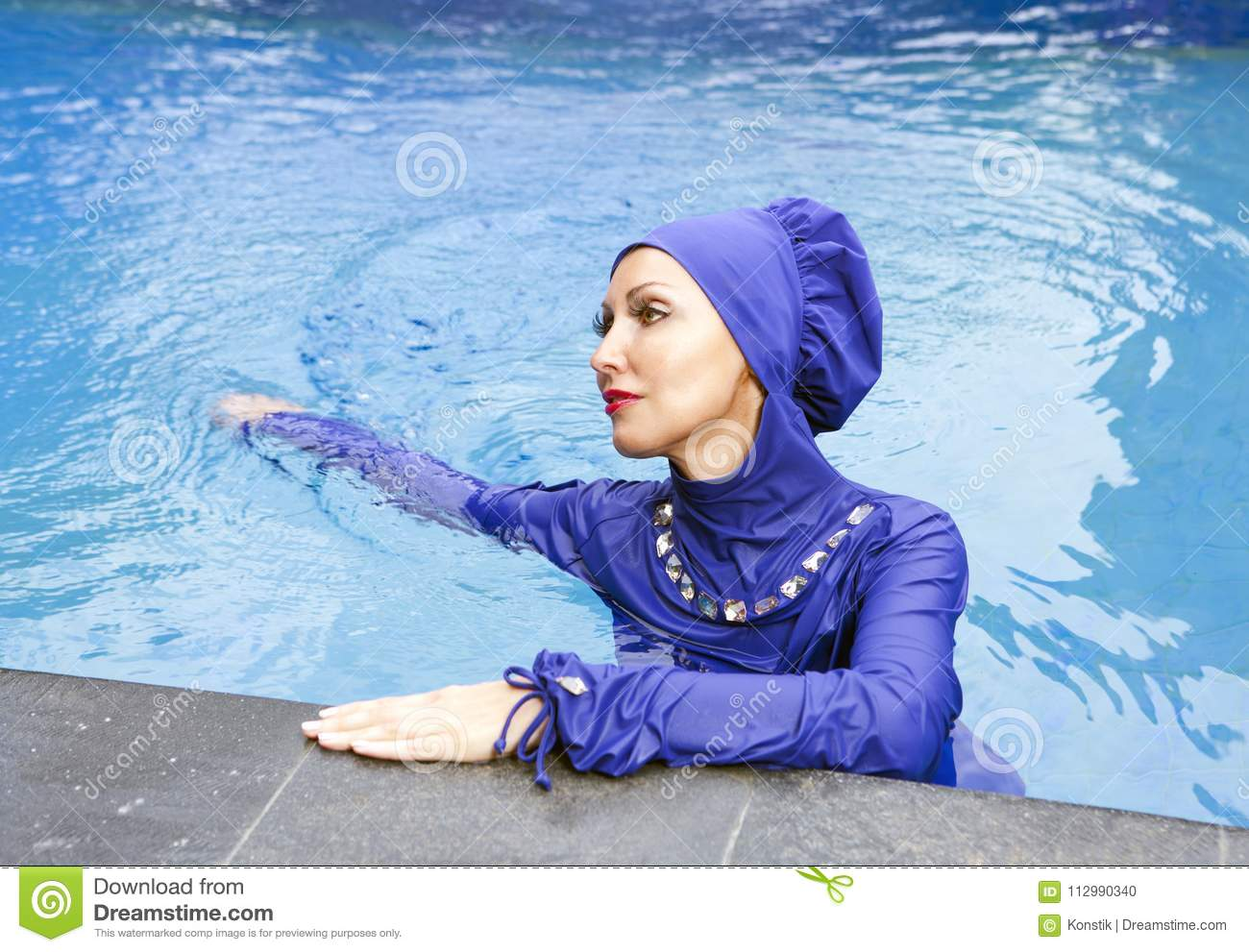 Attractive woman in a Muslim swimwear burkini swims in the pool