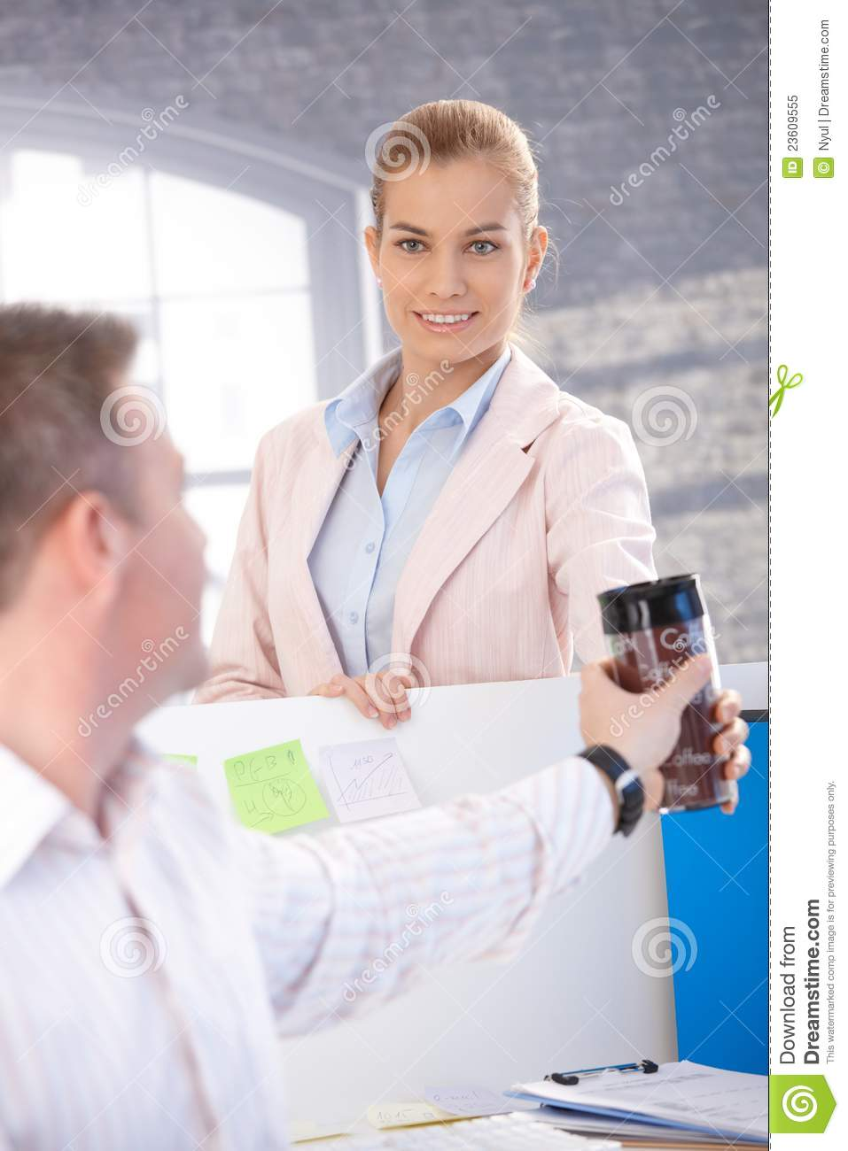 Attractive Woman Passing Coffee To Colleague Royalty Free