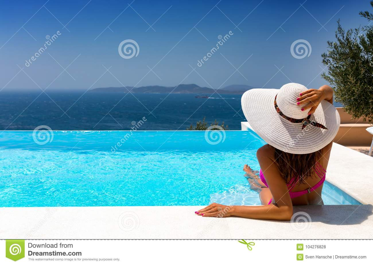 Attractive woman is relaxing in an infinity pool