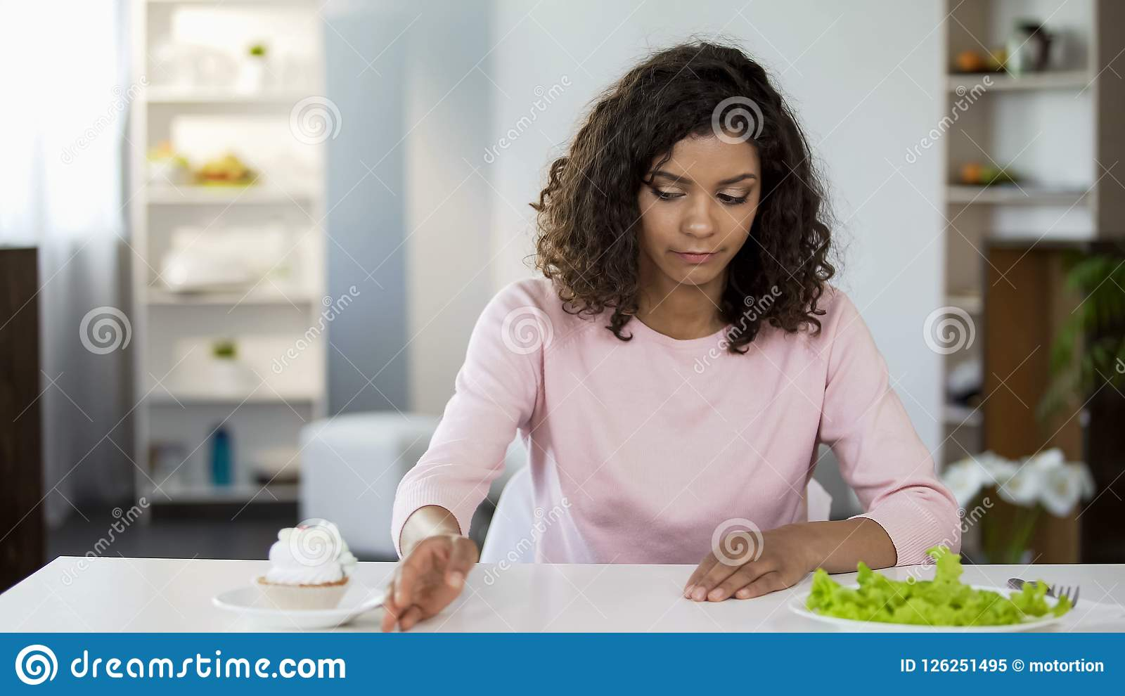 Attractive woman sadly choosing salad over cake, weight control, diet nutrition