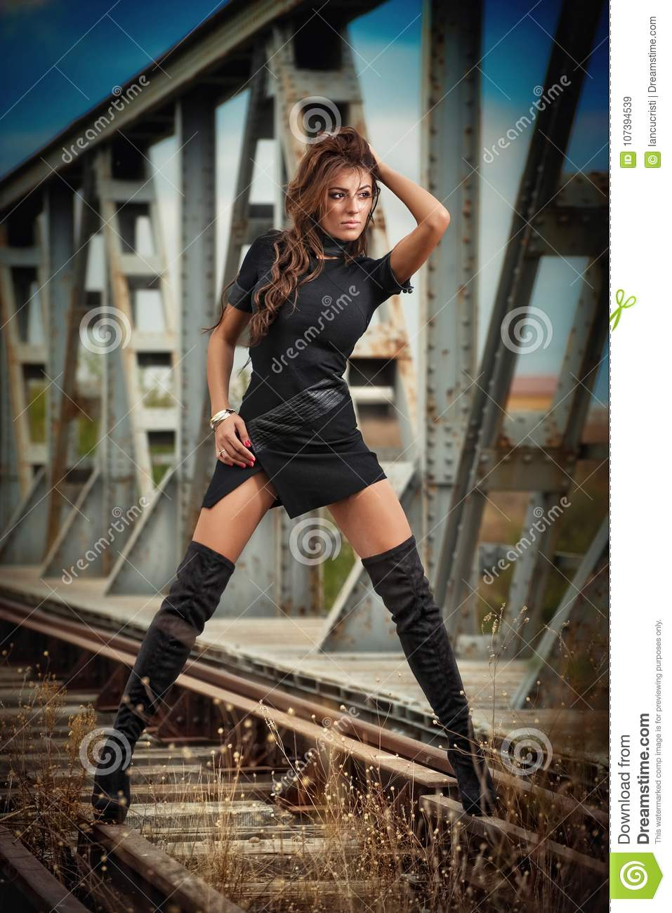21e65900df Attractive woman with short black dress and long leather boots standing on  the rails with bridge in background. Fashion girl , on the bridge posing in  black ...