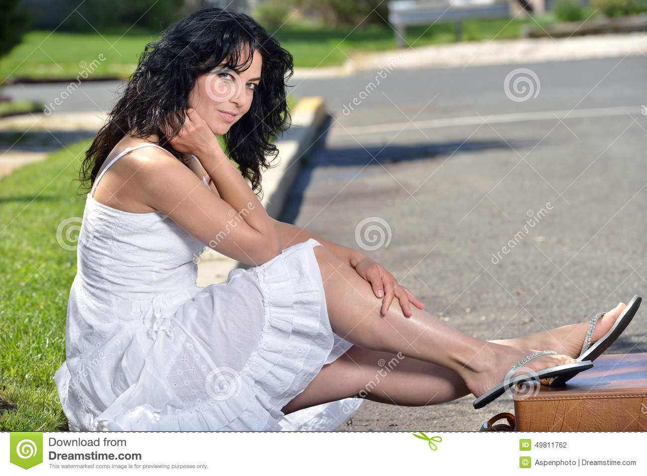 attractive woman sits on curb stock photo - image of trip, female