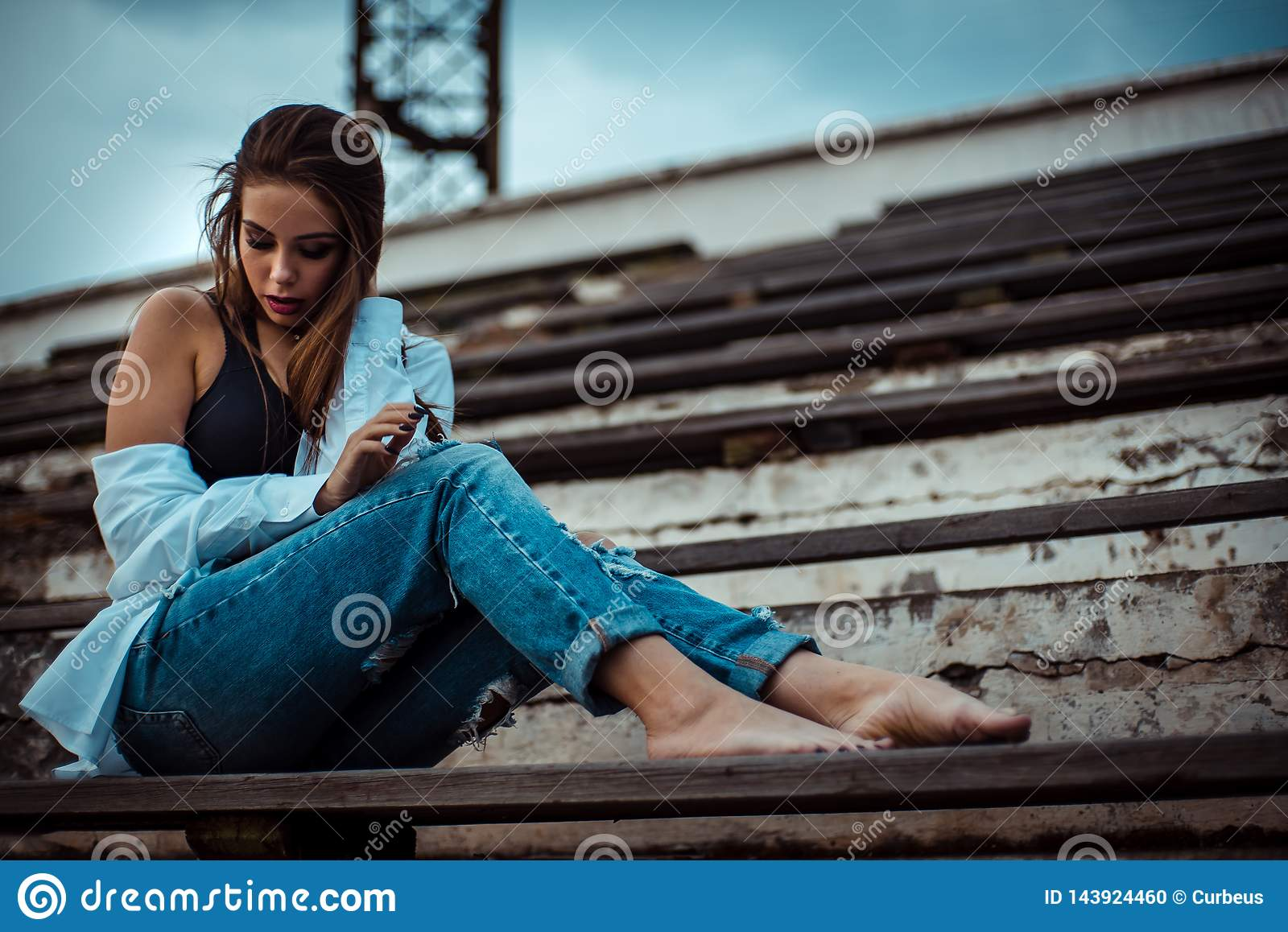 Attractive woman sitting with bare feet in the stadium. She`s wearing a shirt and jeans
