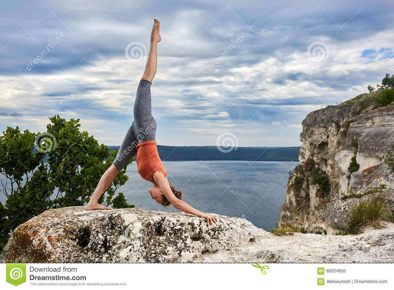 Attractive woman standing on the rock and doing yoga exercises above river.